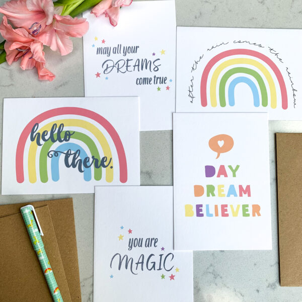 Postcards with positive messages and rainbows on them, flatlay with flower in the top left corner